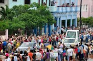 "Cubans wave to Pope Benedict XVI as he leaves in his Popemobile in Havana. Pope Benedict XVI on Wednesday wrapped up a visit to Cuba with a call for respect of ""basic freedoms,"" pursuing his persistent prodding of the island's Communist authorities to embrace change"