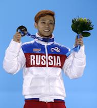 Viktor Ahn of Russia, who won the bronze medal in the men's 1,500-meter short track speedskating holds his medal during the medals ceremony at the 2014 Winter Olympics, Monday, Feb. 10, 2014, in Sochi, Russia. (AP Photo/Morry Gash)