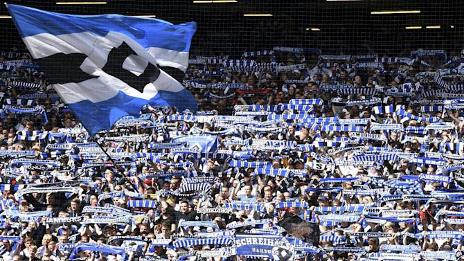 Hamburg SV supporters cheer for their team in the stands ahead of their German Bundesliga first division soccer match against Schalke 04 in Hamburg, Germany