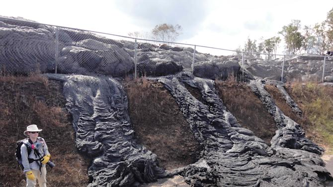 This Nov. 16, 2014 photo provided by the U.S. Geological Survey shows lava flow from the Kilauea Volcano that began on June 27 as it passes a fence to the Pahoa transfer station in Pahoa, Hawaii. Kilauea has been erupting continuously for more than 31 years. (AP Photo/U.S. Geological Survey)