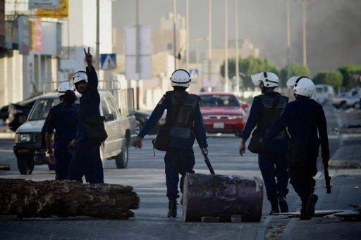 A Bahraini riot policeman flashes the victory sign during clashes with Shiite protesters in solidarity with jailed Bahraini opposition activists in Malekia, on the outskirts of Manama on September 4