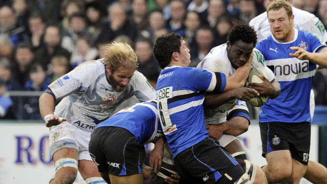 CORRECTS IDENTITY Bath's Francois Louw, centre, and Olly Woodburn, 2nd left, tackle Montpellier's Fulgence Ouedraogo during their Heineken Cup pool 3 rugby match at the Recreation ground, Bath, England, Sunday, Nov. 20, 2011. (AP Photo/Tom Hevezi)