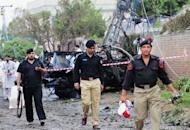 Pakistani policemen collect evidence at a bomb blast site in Peshawar. A suicide car bomber rammed a US consulate vehicle in Pakistan on Monday, killing at least two people in the deadliest attack targeting Americans in the country in more than two years