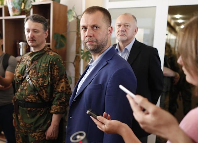 Alexander Borodai, center, Prime Minister of the self proclaimed 'Donetsk people's republic', listens for a question during his and Igor Strelkov, a pro-Russian separatist commander, left,
