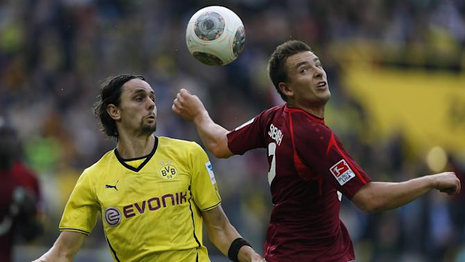 Dortmund's Neven Subotic of Serbia, left, and Hannover's Leon Andreasen of Denmark challenge for the ball during the German first division Bundesliga soccer match between BvB Borussia Dortmund and Hannover 96 in Dortmund, Germany, Saturday, Oct. 19, 2013
