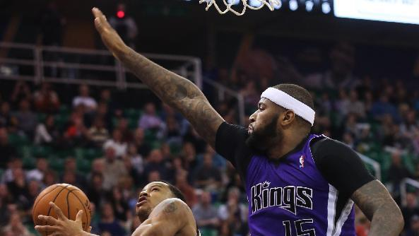 Sacramento Kings' DeMarcus Cousins (15) and Sacramento Kings' Derrick Williams (13) defend as Utah Jazz's Trey Burke (3) takes a shot in the second half of an NBA basketball game on Saturday, Dec. 7, 2013, in Salt Lake City. The Kings went on to win 112-102 in overtime