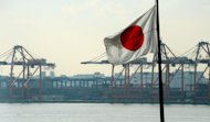 Japan's national flag flies in front of the container pier of Tokyo port, on January 24, 2013. Japan's current account surplus last year shrank to its lowest in almost three decades, data showed on Friday, as exports to China and Europe slumped in a worrying sign for the world's third-largest economy