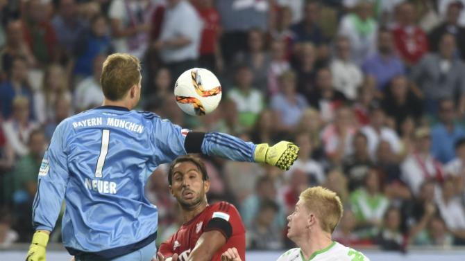 Bayern Munich's goalkeeper Neuer and Benatia challenge VfL Wolfsburg's De Bruyne during German Supercup soccer match in Wolfsburg