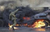 A protester throws stones as a vehicle is on fire during clashes with anti-government protesters in Kiev February 18, 2014. REUTERS/Konstantin Chernichkin