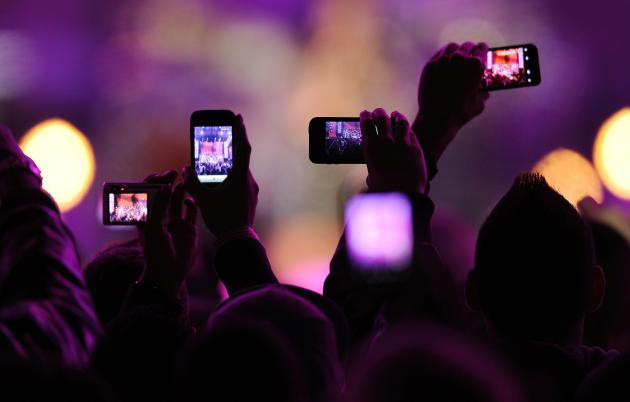 "Fans take photos with their mobile phones during the VH1 ""Divas Salute The Troops"" show at the Marine Corps Air Station Miramar in San Diego, in this December 3, 2010, file photo. Snapchat, the mobile photo-sharing service beloved by teenagers and twenty-somethings, has raised another $50 million, according to a Securities and Exchange Commission filing made December 11, 2013. The funding brings the total raised by the two-year-old company to more than $123 million. REUTERS/K.C. Alfred/Files (UNITED STATES - Tags: ENTERTAINMENT SCIENCE TECHNOLOGY)"