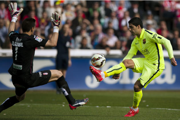 Barcelona's Luis Suarez, right, in action with Granada's goalkeeper Oier Olazabal, left, during a Spanish La Liga soccer match between Granada and FC Barcelona at Los Carmenes stadium in Grana