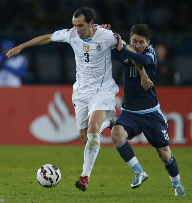 Uruguay's Godin and Argentina's Messi fight for the ball during their first round Copa America 2015 soccer match at Estadio La Portada in La...