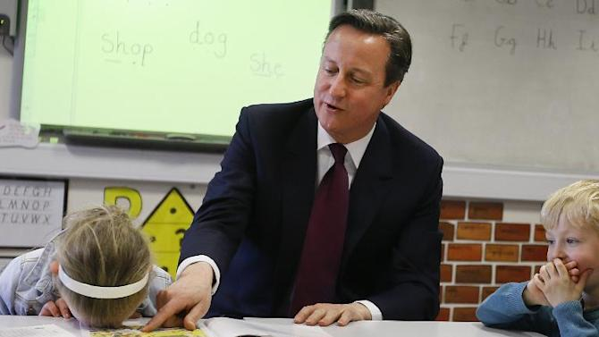 Britain's Prime Minister David Cameron reads a book to children during a visit to Sacred Heart RC primary school in Westhoughton near Bolton on April 8, 2015