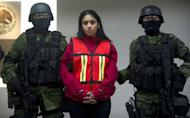 """Mexican Army soldiers guard Irasema Lopez Garza, partner of Carlos Oliva Castillo, aka """"La Rana"""", alleged leader of the Zetas in the states of Coahuila, Nuevo Leon y Tamaulipas, in Mexico City, in 2011. The high mortality rate in Mexico's drug war has seen women progress quickly in the shadowy underworld of the cartels and they are increasingly taking on key management roles, a new book says"""