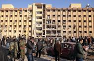 Syrians gather at the scene of an explosion outside Aleppo University, between the university dormitories and the architecture faculty, on January 15, 2013. Twin blasts ripped through the university campus killing at least 82 people and wounding scores more, the provincial governor said