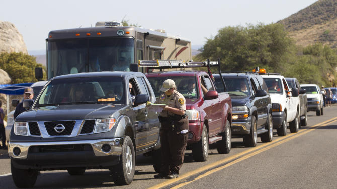 Residents have their identification checked at a check point on Hwy 89 near outside of Yarnell, Ariz. on Monday, July 8, 2013, as evacuees from Yarnell and Illah are let back into their homes after being evacuated June 30. Nineteen members of the Granite Mountain Hotshot crew died fighting the Yarnell Hills Fire, about 40 miles southwest of Prescott. (AP Photo/The Arizona Republic, Michael Chow) MARICOPA COUNTY OUT; MAGS OUT; NO SALES