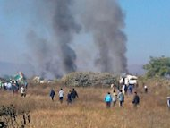 This photo, taken with a camera phone on December 25, 2012, shows smoke rising from the scene of an Air Bagan passenger plane crash near Heho airport in Myanmar's eastern Shan state. The plane, carrying 65 passengers including foreign tourists, crash-landed, leaving two people dead and 11 others injured.