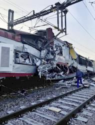 In this image provided by the Luxembourg Police Grand Ducale, a man walks near the wreckage of a passenger train and a freight train after they collided in Bettemberg, Luxembourg on Tuesday, Feb. 14, 2017. The collision left one person dead and at least four injured. (Luxembourg Police Grand Ducale via AP)