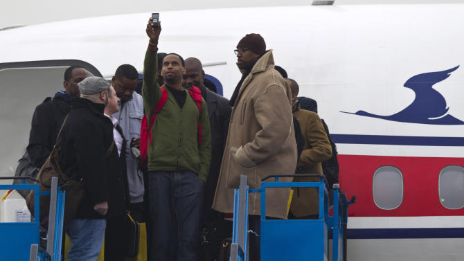 """U.S. basketball player Jerry Dupree, center, uses a mobile camera to take a photograph as he and fellow players including former NBA player Vin Baker, right, arrive at the international airport in Pyongyang, North Korea, Monday, Jan. 6, 2014. Dennis Rodman arrived in the North Korean with a squad of former basketball stars in what Rodman calls """"basketball diplomacy,"""" although U.S. officials have criticized his efforts. (AP Photo/Kim Kwang Hyon)"""