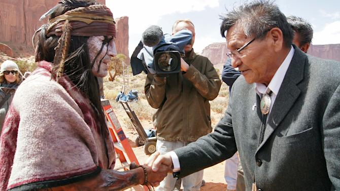 """This April 2012 photo released by the Navajo Nation shows, actor Johnny Depp shaking hands with Navajo Nation President Ben Shelly in Monument Valley during the filming of """"The Lone Ranger."""" The Pendleton blanket was presented to Johnny Depp as a good will gesture on behalf of the Navajo Nation.  (AP Photo/Emerald Craig, Navajo Nation)"""
