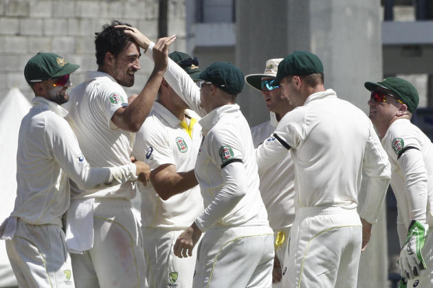 Australia bowler Mitchell Starc, second left, celebrates with teammates after taking the wicket of West Indies' Jason Holder, who was caught by Mitchell Marsh for 21 runs, during the opening day o