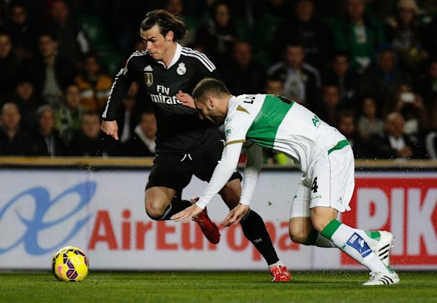 Real Madrid forward Gareth Bale (L) skips past Elche defender Lomban during the Spanish La Liga match at the Martin Valero stadium in Elche on February 22, 2015