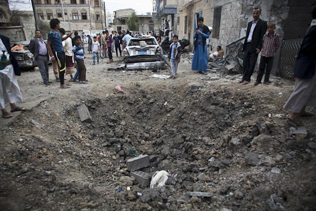 People stand around a crater made by a Saudi-led coalition airstrike in Sanaa, Yemen, Wednesday, May 27, 2015. In a new report Wednesday, World Health Organization Chief Margaret Chan said that Yemen&