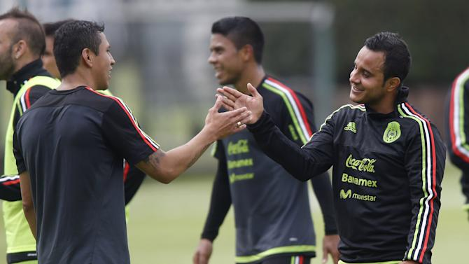 Mexico's Luis Montes interacts with teammate Julio Cesar Dominguez during a practice session in Mexico City
