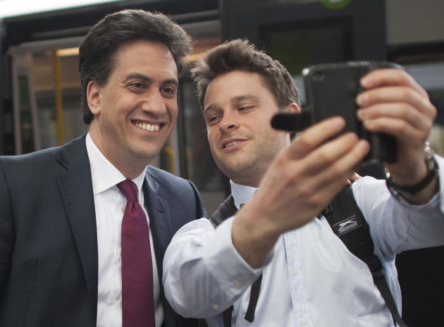 Britain's Labour Party  leader Ed Miliband, left, poses for a picture at Nuneaton railway station  before unveiling  his party's new National Health Service campaign posters  in Nuneaton centr