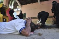 An inmate lies on the ground as a policeman holds handcuffs after a gunfight in the Tuxpan prison in Iguala, in the Mexican State of Guerrero January 3, 2014. REUTERS/Jesus Solano