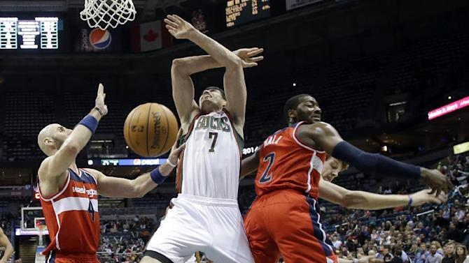 Milwaukee Bucks' Ersan Ilyasova (7) battles for a rebound with Washington Wizards' John Wall (2) and Marcin Gortat (4) during the second half of an NBA basketball game Wednesday, Nov. 27, 2013, in Milwaukee