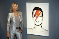 Model Kate Moss poses with Kate 'Aladdin Sane', 2003, by photographer Nick Knight, at Christie's auction house in London September 4, 2013. REUTERS/Luke MacGregor/Files
