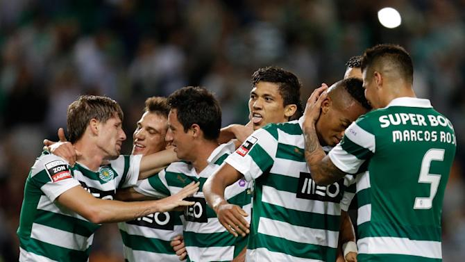 Sporting's Montero, from Colombia, center, sticks his tongue out while celebrating after scoring his second goal against Setubal  during their Portuguese league soccer match Saturday, Oct. 5 2013, at Sporting's Alvalade stadium in Lisbon