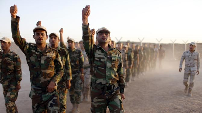 Kurdish Peshmerga fighters march during training before deploying to fight the Islamic State, at a temporary military camp near the front line in Gwar