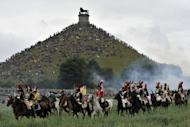 People sit on the Lion's Mound, around the lion monument of the Battle of Waterloo during a re-enactment in 2010. Almost 200 years after the French cavalry charge, bulldozers are rolling into action to spruce up the memorial site of the battle that humbled Napoleon