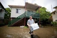 Local resident walks through floodwaters carrying some belongings, outside his Cullen Street home, in the inner Brisbane suburb of Newmarket on January 28, 2013. Helicopters have plucked dozens of stranded Australians to safety in dramatic rooftop rescues as severe floods swept the northeast, killing four people and inundating thousands of homes