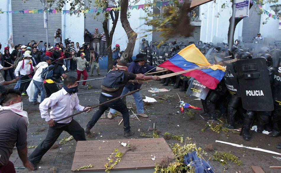 Demonstrators clash with police during a march in Quito