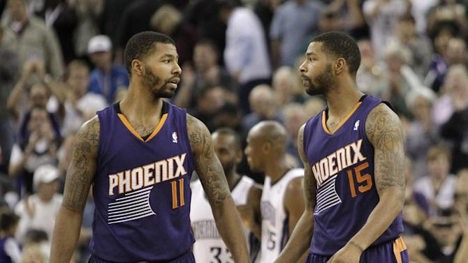 Phoenix Suns' Markieff Morris, left, shakes hands with his twin brother Marcus, as they walk off the court after the Suns 107-104 loss to the Sacramento King in a NBA basketball game in Sacramento, Calif., Tuesday, Nov. 19, 2013
