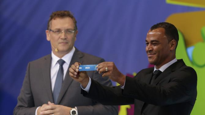 "Cafu holds the slip showing ""Brazil"" during the draw for the 2014 World Cup in Sao Joao da Mata"