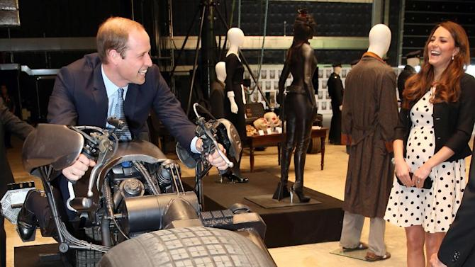 "Britain's Kate the Duchess of Cambridge watches her husband Prince William as he sits on the 'Batpod' during the inauguration of ""Warner Bros. Studios Leavesden"" near Watford, approximately 18 miles north west of central London, Friday, April 26, 2013. As well as attending the inauguration Friday at the former World War II airfield site, the royals will undertake a tour of Warner Bros. ""Studio Tour London - The Making of Harry Potter"", where they will view props, costumes and models from the Harry Potter film series. (AP Photo/Chris Jackson, Pool)"