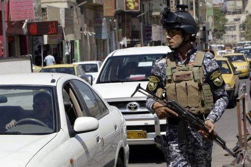 An Iraqi police officer guards a checkpoint in central Baghdad on August 4, 2012. A car bomb at an Iraqi Kurdish political party headquarters in the town of Jalawla killed two Kurdish security recruits and wounded two on Sunday, security and medical officials said.