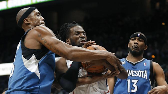 Atlanta Hawks forward DeMarre Carroll, center, and Minnesota Timberwolves forward Dante Cunningham, left, struggle for control of the ball as Corey Brewer (13) watches during the second half of an NBA basketball game Saturday, Feb. 1, 2014, in Atlanta. Atlanta won 120-113