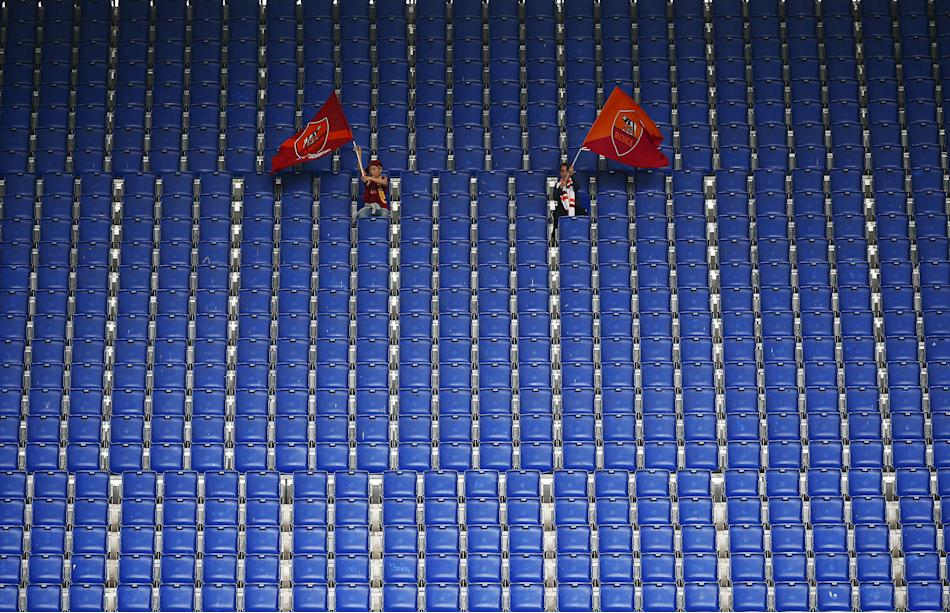 AS Roma's fans wave flags as they stand in the tribune during their Italian Serie A soccer match against Atalanta at Olympic stadium in Rome