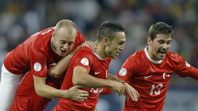 Turkey's Mevlut Erdinc, center, celebrates scoring his team's second goal during a World Cup Group D qualifying soccer match against Romania at the National Arena stadium in Bucharest, Romania, Tuesday, Sept. 10, 2013. Turkey defeated Romania 2-0