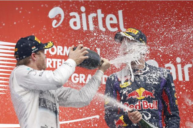 Mercedes Formula One driver Rosberg sprays champagne on the face of Red Bull Formula One driver Vettel on the podium after the Indian F1 Grand Prix at the Buddh International Circuit in Greater Noida