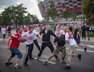 Polish football fans beat a Russian football fan during clashes in Warsaw. Police used an arsenal of tear gas, water cannon, rubber bullets and pepper spray and detained dozens of brawling football fans ahead of a key Euro 2012 match between Poland and Russia on Tuesday