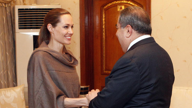 United Nations High Commissioner for Refugees (UNHCR) special envoy Angelina Jolie, left, shakes hands with Iraqi Foreign Minister Hoshyar Zebari in Baghdad, Iraq, Saturday, Sept. 15. Jolie said Friday that with winter approaching, she is concerned about the plight of hundreds of thousands of Syrians forced to flee their homes.(AP Photo/Karim Kadim)