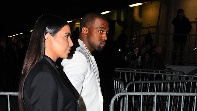 Kim Kardashian and Kanye West arrive at Givenchy's Ready to Wear's Fall-Winter 2013-2014 fashion collection presented Sunday, March 3, 2013 in Paris. (AP Photo/Zacharie Scheurer)