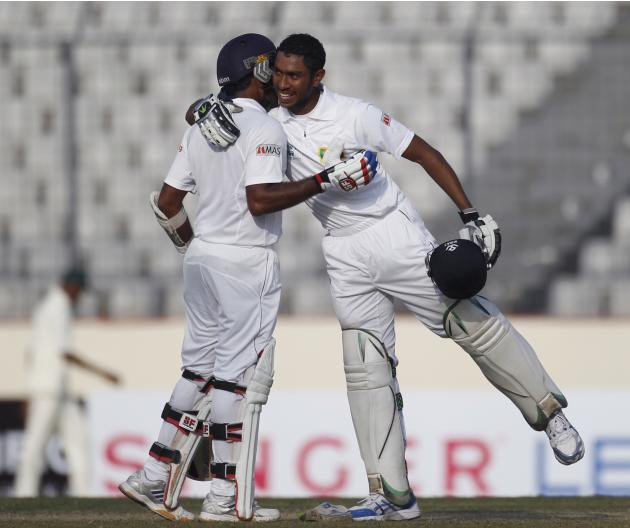 Sri Lanka's Jayawardene congratulates teammate Vithanage for scoring a century during the third day of their first test cricket match of the series against Bangladesh in Dhaka