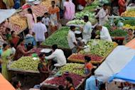 People shop at a fruit and vegetable market in Ahmedabad, India. While other central banks around the globe have been easing interest rates to revive their troubled economies, the RBI has said that economic reforms are needed first in order to to remove chronic bottlenecks in the economy